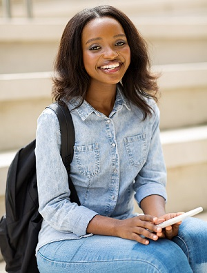 portrait of happy young african college student holding cell phone